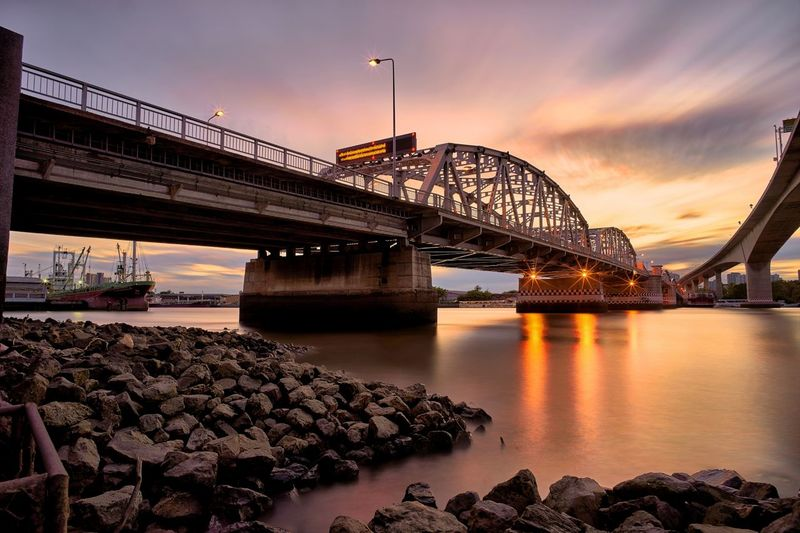 City Cityscape Sunset Water Illuminated Urban Skyline Bridge - Man Made Structure Business Finance And Industry Railroad Track Long Exposure
