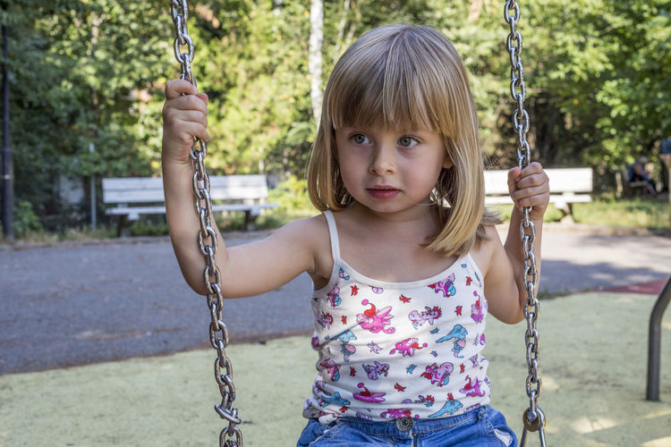 Portrait Of Girl On Swing At The Playground