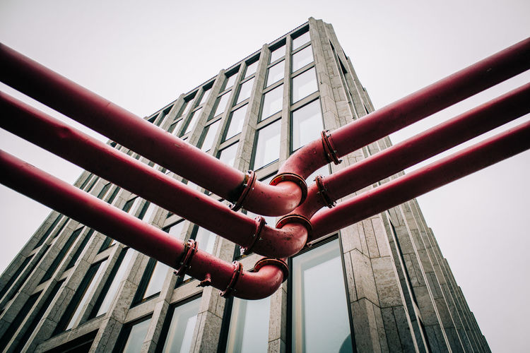 Low angle view of pipes and building against clear sky in city