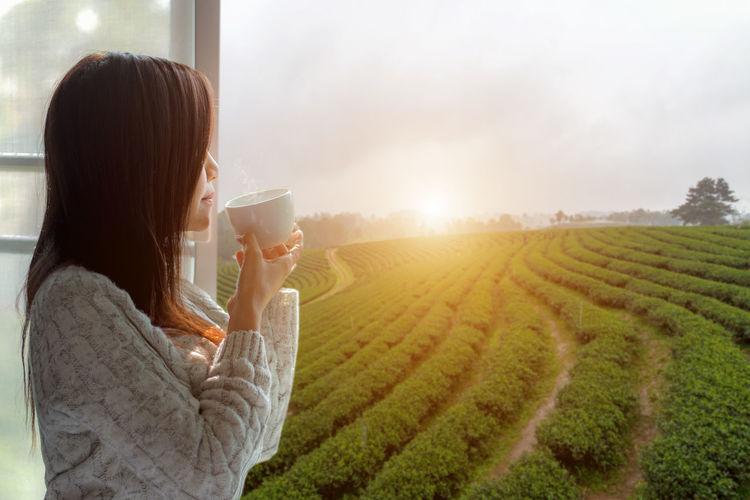 Woman drinking coffee in field