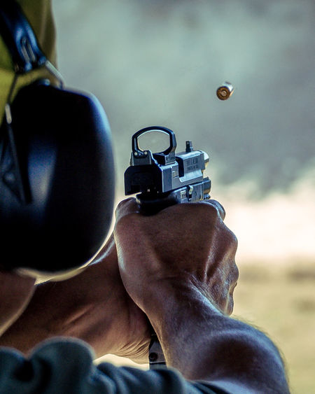 Adult Adults Only Close-up Compete Competition Conflict Day Handgun Holding Human Body Part Human Hand Indoors  Leisure Activity Lifestyles Marksman Men One Man Only One Person Only Men People Pistol Real People Shooting Weapon Weapons