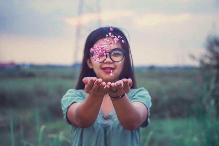 Portrait of a girl wearing sunglasses on field
