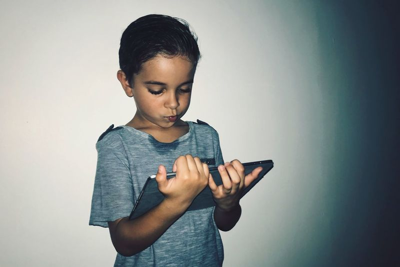 Boy holding smart phone while standing against wall