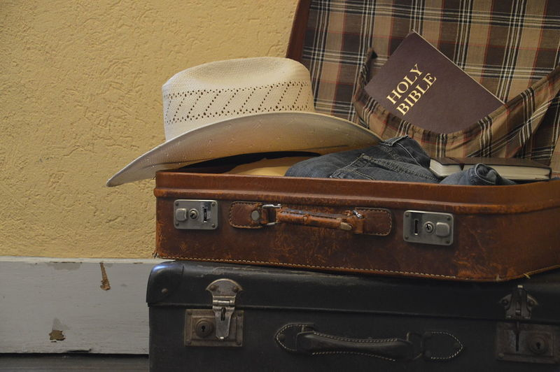 Suitcase filled for a mission trip with clothes, hat and a bible Christian Christianity Holidays Leather Mission Outreach Purpose Travel Trip Bag Bible Clothes Evangelism Great Commission Journey Missionary Old Packing Preparation  Prepare Religious  Straw Hat Suitcase Vacation Vision