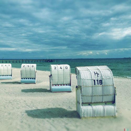 Seats on sand at beach against clouds
