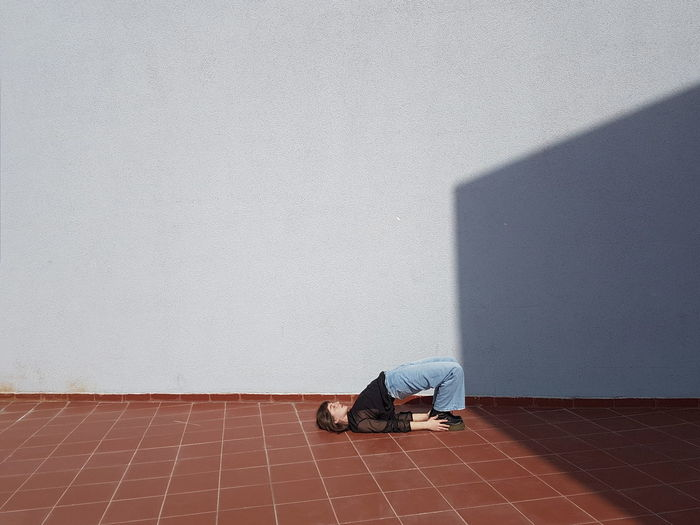 Woman stretching body against wall