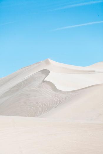 Sand dunes in desert against clear blue sky