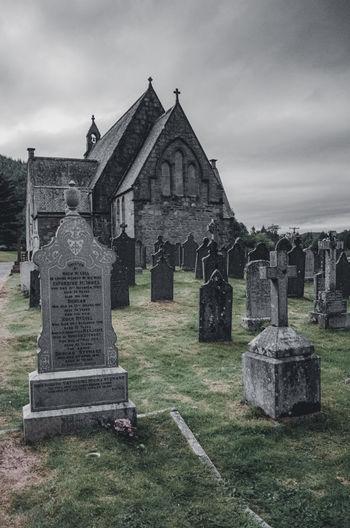 Stone cross on cemetery against sky