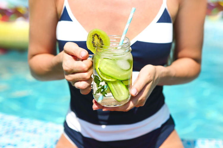 Midsection of woman holding drink in swimming pool