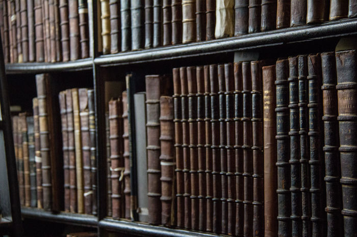 Books in a shelf Antique Archives Backgrounds Book Bookshelf Close-up Collection Day Education Full Frame Hardcover Book History In A Row Indoors  Intelligence Large Group Of Objects Learning Leather Library Literature Research Trinity College Trinitycollege University Wisdom