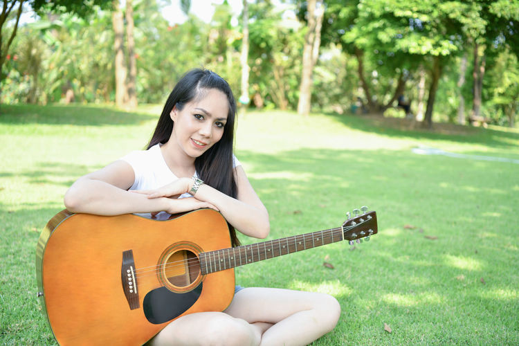 Portrait of young woman with guitar sitting against trees at park