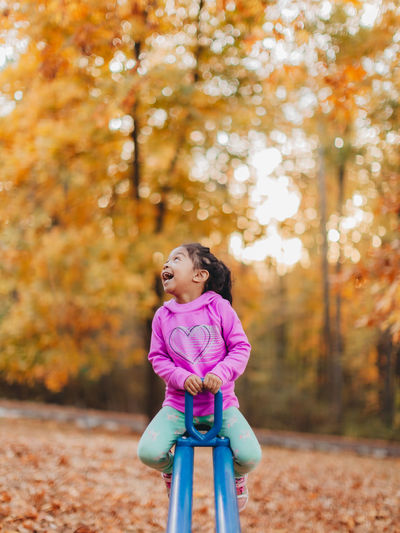 Girl looking away on tree during autumn