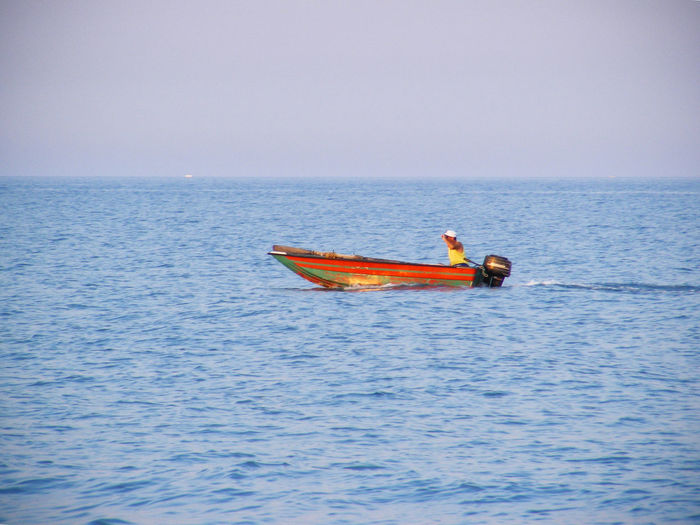 Blue Boat Clear Sky Day Fisherman Horizon Over Water Lifestyles Men Mode Of Transport Nautical Vessel Orange Color Sea Seascape Tranquil Scene Transportation Water Waterfront