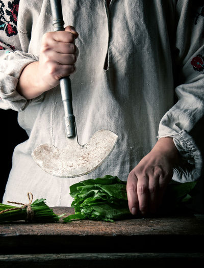 Midsection of woman cutting vegetables on cutting board