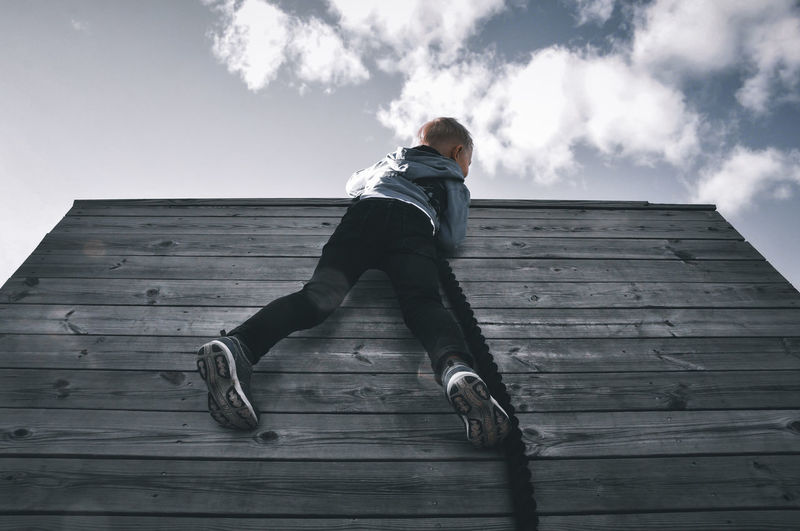 Low angle view of woman climbing on wood against sky