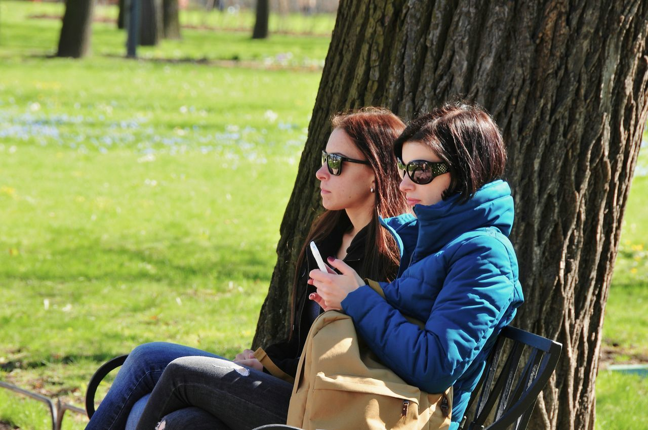 sitting, tree trunk, togetherness, leisure activity, casual clothing, tree, grass, real people, two people, day, side view, lifestyles, outdoors, bonding, love, smiling, happiness, childhood, young women, young adult, nature, wireless technology, people, adult