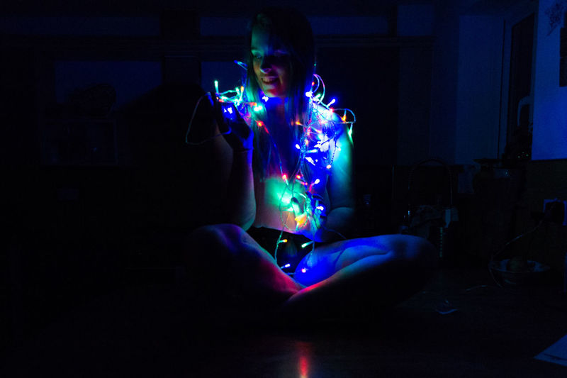 Young woman with illuminated string lights sitting at home