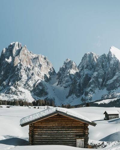 Log cabin against snowcapped mountains