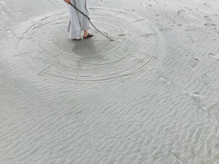 Low section of person walking on beach
