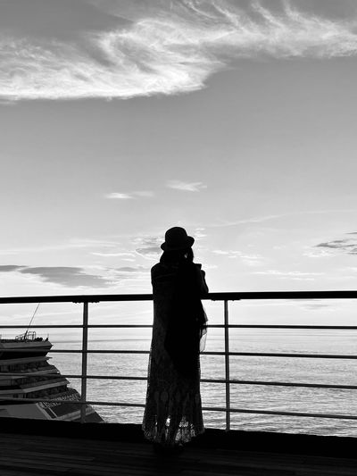 Silhouette woman looking at sea against sky