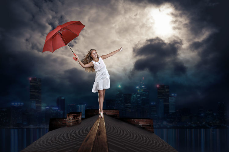 teenage girl with an umbrella on the roof over the night town City, Town, Acrobat, Balance, Child, Childhood, Equilibrist, Female, Fun, Girl, High, Night, Outdoors, Roof, Skyline, Spire, Teenage, Tower, Townhouse, Umbrella, Urban, Walk, Wind Composing Mystical Photoshop Cloud - Sky Sky Full Length City Building Exterior Architecture Young Adult One Person Adult Nature Standing Cityscape Built Structure Protection Women Umbrella Holding Human Arm Limb Outdoors Freedom Human Limb Office Building Exterior Beautiful Woman
