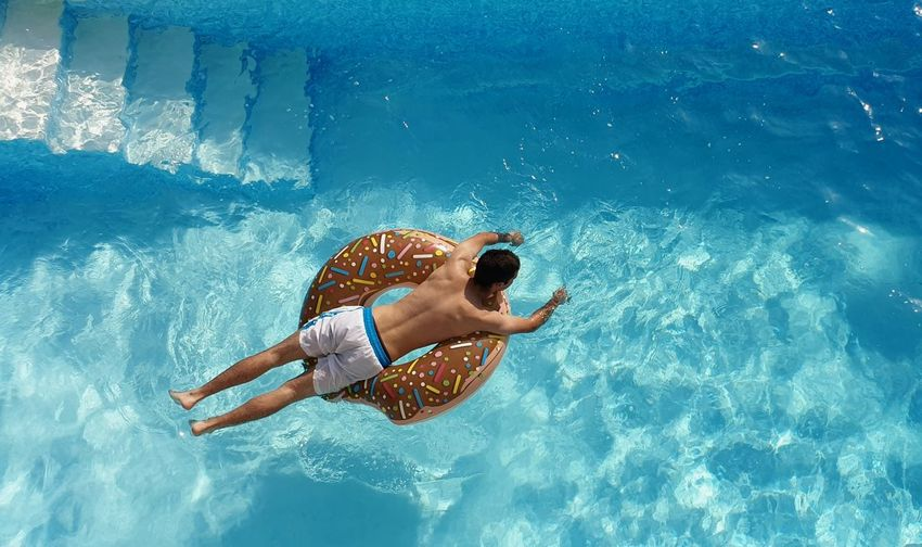 High angle view of man on donut inflatable ring in swimming pool