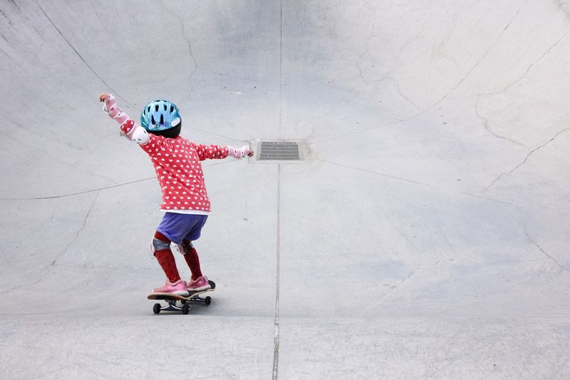 High Angle View Of Child With Skateboard On Ramps