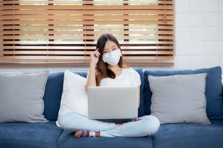 Young woman wearing mask using laptop sitting on sofa at home