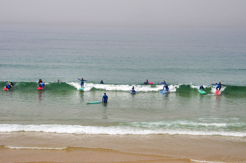 Surfers at portuguese beach, green waves Aquatic Sport Beach Green Waves Group Of People Horizon Horizon Over Water Leisure Activity Sea Sport Surfers Lifestyle Surfers Waiting For Waves Water Wave