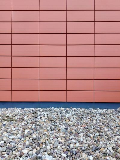 Pebbles and red tiled wall facade