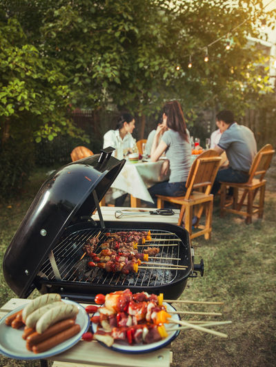 Adult Barbecue Barbecue Grill Day Food Food And Drink Freshness Front Or Back Yard Group Of People Healthy Eating Leisure Activity Lifestyles Meal Meat Men Outdoors People Plate Preparation  Sitting Table Vegetable Women