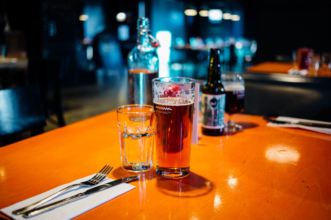 table, food and drink, indoors, drinking glass, refreshment, alcohol, drink, bar, no people, beer, focus on foreground, bar counter, close-up, freshness, ashtray, shot glass, night