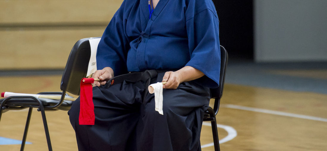 Midsection of karate referee holding flags while sitting on chair