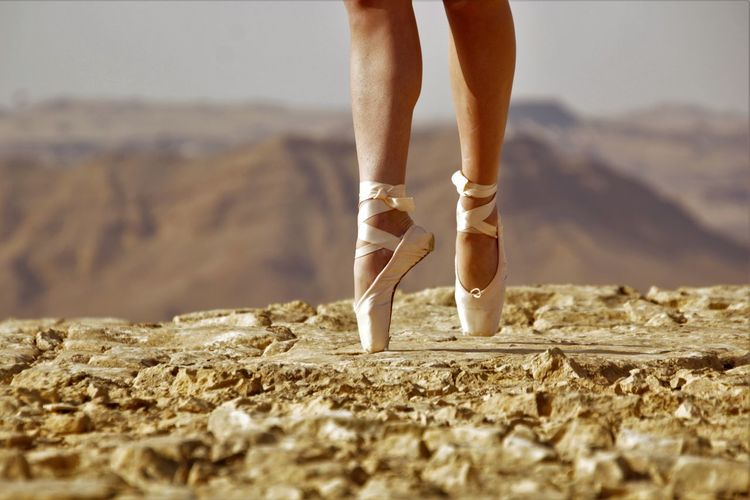 Low section of ballet danger standing tiptoe on rock against mountain