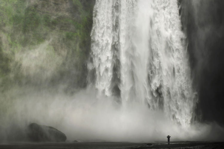 Silhouette man standing in front of majestic skogafoss