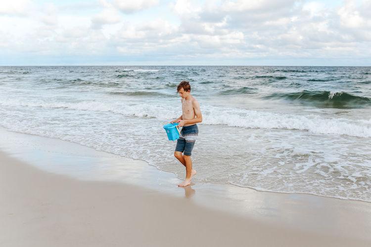 Rear view of boy on beach against sky