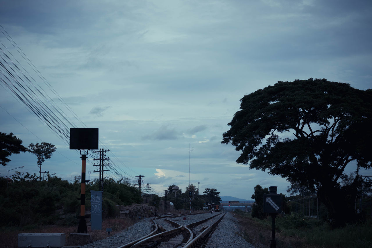 sky, transportation, tree, railroad track, rail transportation, plant, track, cloud - sky, nature, mode of transportation, electricity, cable, electricity pylon, technology, no people, connection, public transportation, outdoors, power line, day, power supply