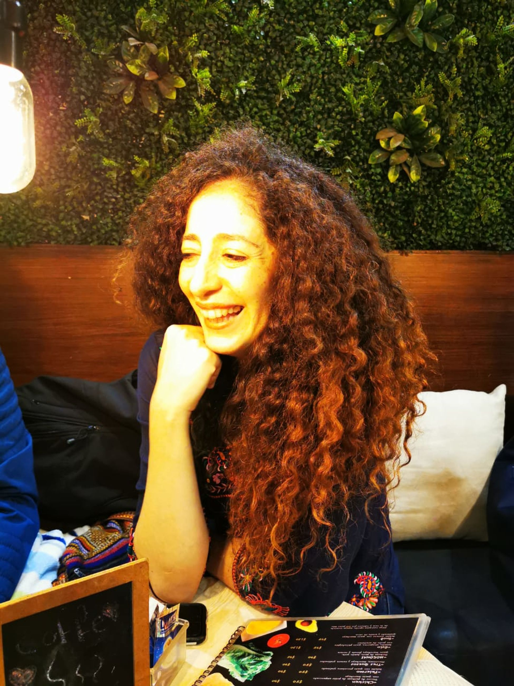 smiling, happiness, one person, young adult, sitting, women, emotion, young women, real people, hair, leisure activity, curly hair, hairstyle, adult, front view, portrait, lifestyles, redhead, casual clothing, cheerful, beautiful woman