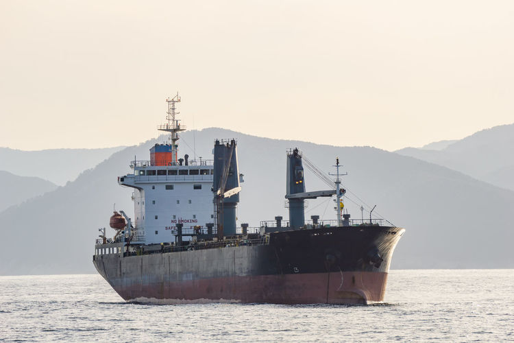 Ship on sea against mountain range