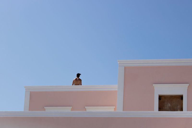 Low angle view of man on terrace against clear sky