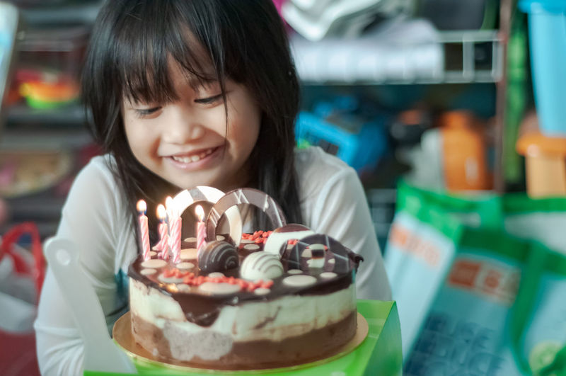 Smiling girl looking at cake