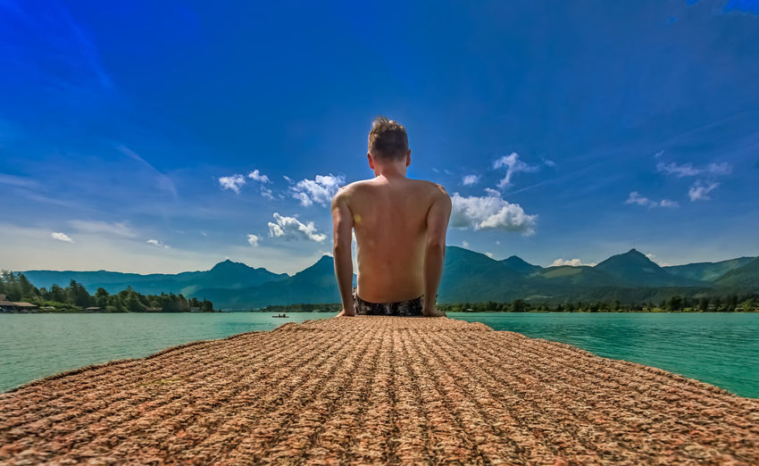 Rear view of shirtless man sitting on jetty against sky