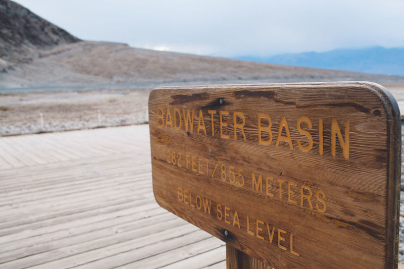 Arid Climate Arid Landscape Bad Water Basin Badwater Basin Beach Communication Day Death Valley Death Valley National Park Death Valley, California Desert Desert Landscape Focus On Foreground Landscape Mountain Nature No People Outdoors Salt Sand Scenics Sea Text Tranquility Wood - Material