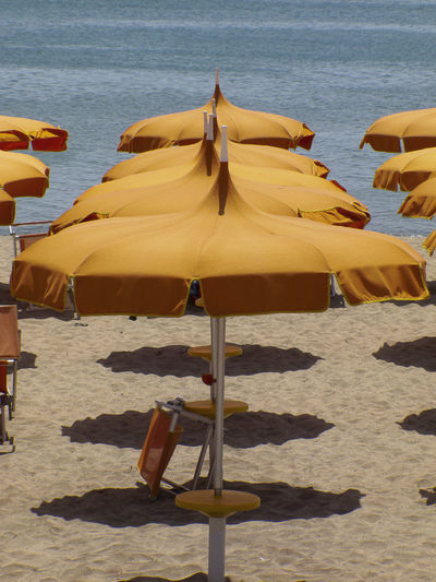 Calabria (Italy): row of orange beach umbrellas waiting for customers Summertime Travel Photography Absence Beach Beach Umbrella Beauty In Nature Blue Water Chair Day Land Nature No People Orange Color Outdoors Parasol Sand Sandy Beach Sea Shade Shadow Sunlight Tranquility Umbrella Water Yellow