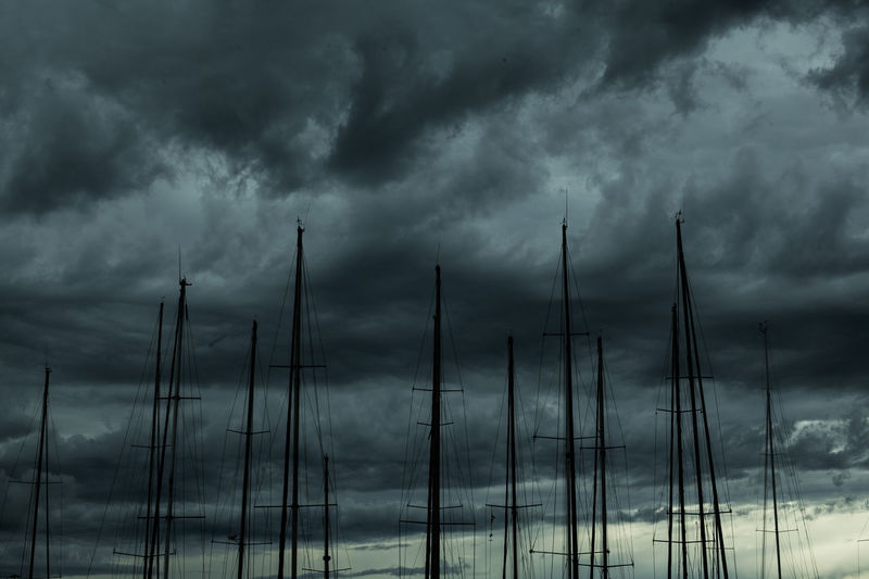 Low angle view of sailboats against cloudy sky