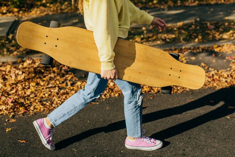 Girl holding a longboard while walking down the street with fall leaves in the background