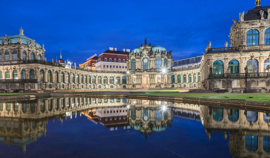 Zwinger museum reflecting on lake against blue sky