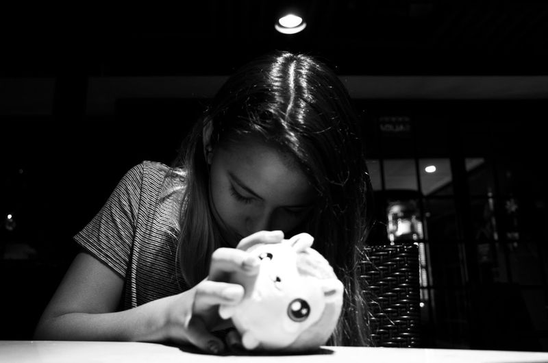 Girl holding toy on table in darkroom at home
