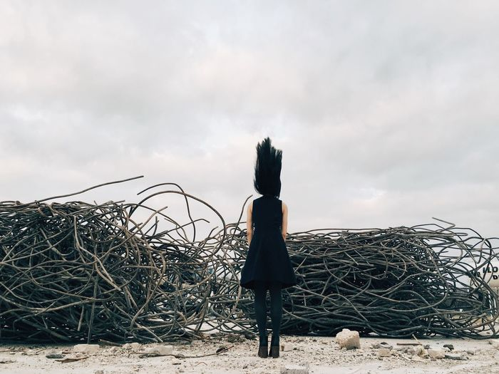 Full Length Rear View Of Woman With Tousled Hair Standing By Abandoned Metal Against Sky