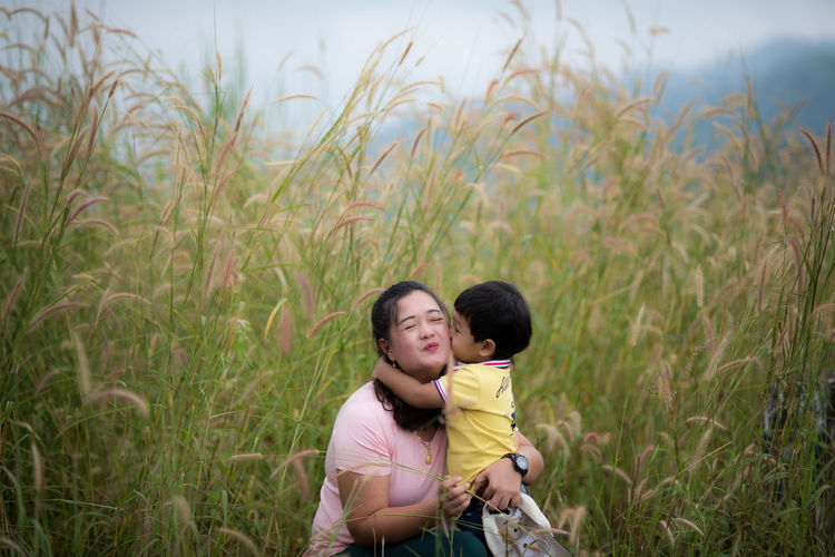 Son kissing mother while standing amidst plants